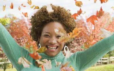 Hispanic woman throwing autumn leaves in air